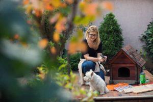Femme en train de construire une niche pour son petit chien blanc dans le jardin